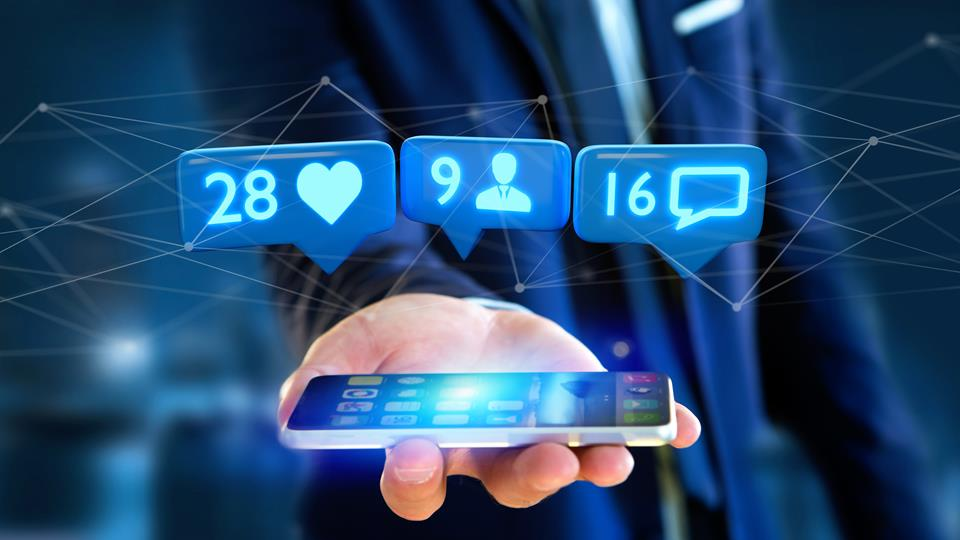 mężczyzna trzymający smartfon ukazukący wirtualne statystyki social media