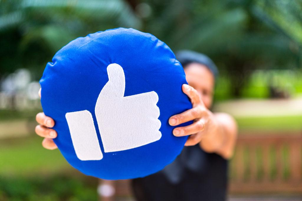 Kobieta trzymająca niebieską poduszkę z emotikoną polubienia z Facebooka.
